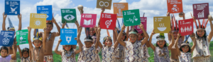 Young peruvian children holding up world goal signs