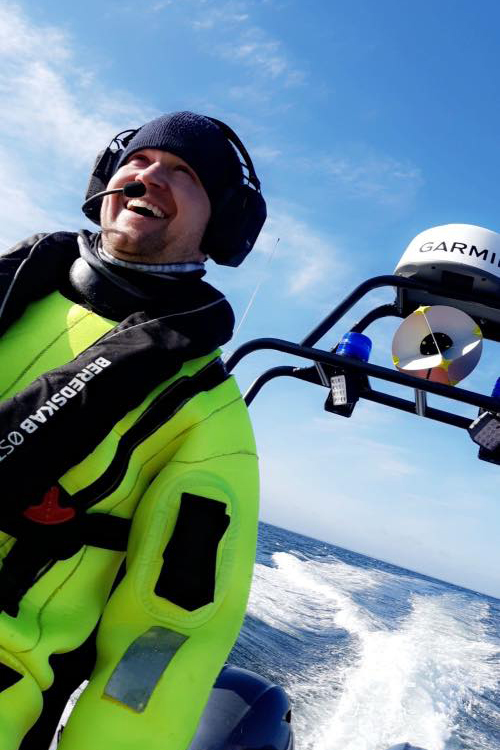 Coast Guard crew smiling with IWCS gear on, while on a boat.