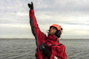 Man pointing to the sky in a drysuit and iwcs headset
